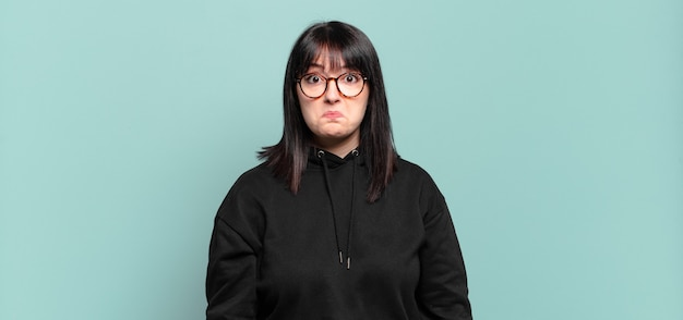 Jolie femme grande taille se sentant triste et stressée, bouleversée à cause d'une mauvaise surprise, avec un regard négatif et anxieux