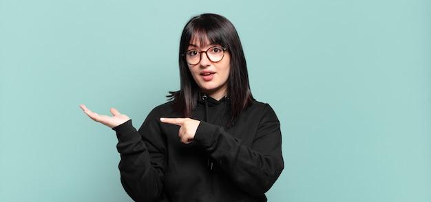 Jolie femme de grande taille souriant joyeusement et pointant pour copier l'espace sur la paume sur le côté, montrant ou faisant la publicité d'un objet