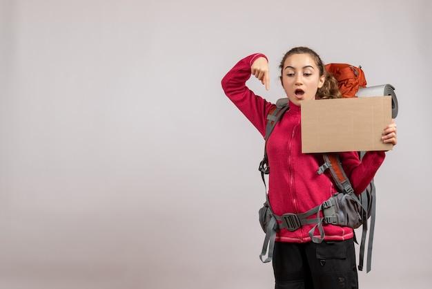 Jolie femme avec un gros sac à dos brandissant un carton pointant ci-dessous
