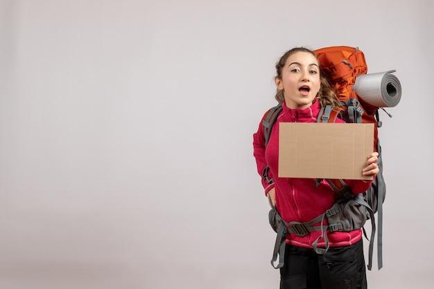 Jolie femme avec un gros sac à dos brandissant du carton sur fond gris