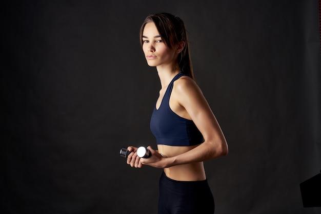 Jolie femme avec des haltères à la main avec des exercices d'entraînement fond isolé