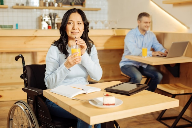 Jolie femme handicapée alerte assis dans un fauteuil roulant et boire du jus tout en travaillant sur sa tablette dans un café et un homme assis en arrière-plan