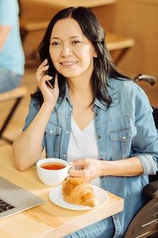 Jolie femme handicapée aux cheveux noirs alerte parler au téléphone et tenant une tasse de café et travaillant sur son ordinateur portable dans un café
