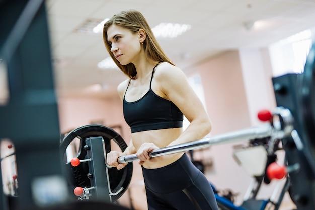 Jolie femme en haut noir et leggings est debout à la barre d'haltères dans la salle de gym. une sportive mince fait de l'exercice dans le centre de remise en forme et se tourne vers l'avenir.