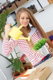 Jolie femme avec de l'herbe avec un arrosoir
