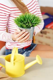 Jolie femme avec de l'herbe avec pot de plantes