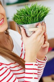 Jolie femme avec de l'herbe avec pot