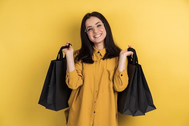 Jolie femme heureuse et élégante accro du shopping dans des verres tenant des sacs à provisions sur le mur orange du studio, isolé