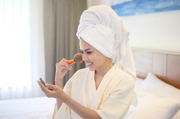 Jolie femme heureuse en peignoir blanc applique un maquillage naturel avec un pinceau à poudre cosmétique, beauty concept.