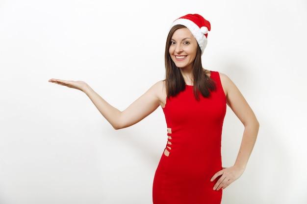 Jolie femme heureuse de race blanche avec un sourire charmant portant une robe rouge et un chapeau de noël regardant la caméra, tenant un espace de copie sur la paume isolé sur fond blanc. fille du père noël. concept de vacances de nouvel an 2018.