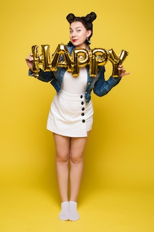 Jolie femme heureuse en riant tenant de grosses lettres d'or posant sur fond de studio jaune