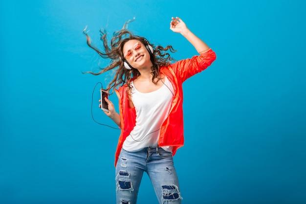 Jolie femme heureuse souriante dansant en écoutant de la musique dans des écouteurs habillés en tenue de style hipster isolé sur fond bleu studio, portant une veste rose et des lunettes de soleil