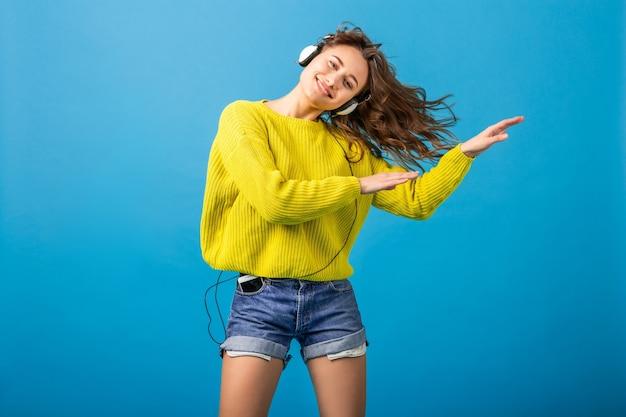 Jolie femme heureuse souriante dansant en écoutant de la musique dans des écouteurs en tenue élégante hipster isolée sur fond bleu studio, portant des shorts et un pull jaune