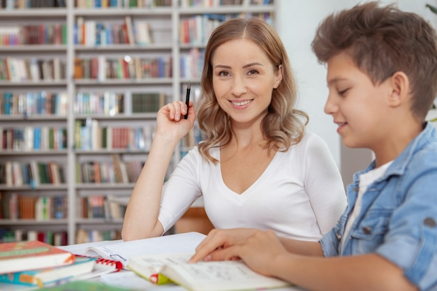 Jolie femme heureuse souriante pendant que son fils lit un livre à la bibliothèque