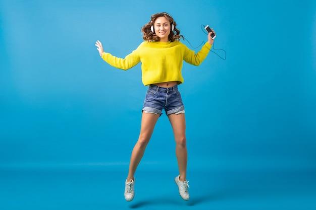 Jolie femme heureuse souriante sautant danser en écoutant de la musique dans des écouteurs en tenue de hipster isolé sur fond bleu studio, portant des shorts et un pull jaune