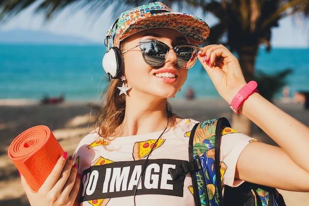 Jolie femme hipster marchant sur la plage en écoutant de la musique sur des écouteurs dans une tenue élégante et cool sur des vacances tropicales d'été ensoleillées portant des accessoires de lunettes de soleil, souriant heureux tenant un tapis de yoga