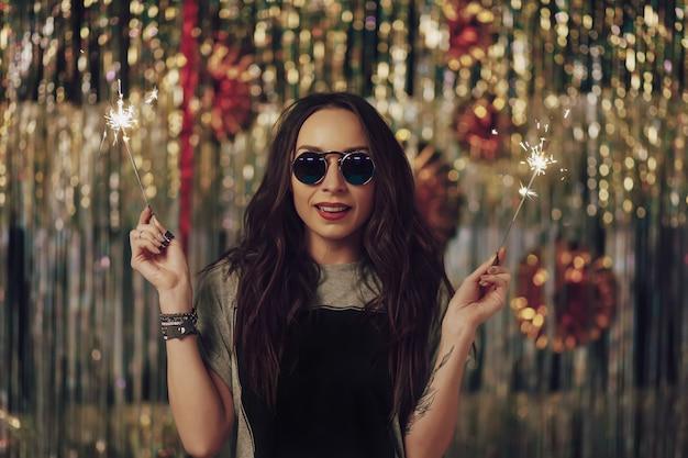 Jolie femme hipster tenant des cierges magiques dans les mains