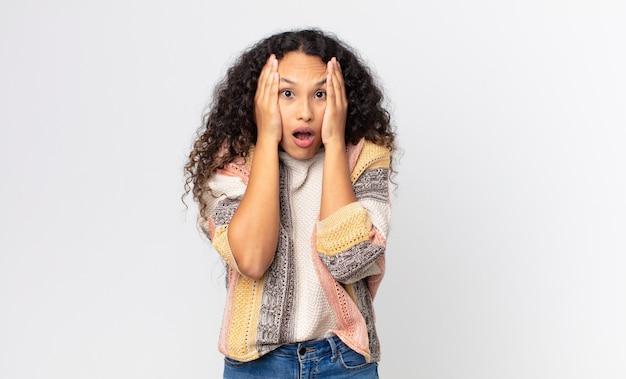 Jolie femme hispanique à l'air désagréablement choquée, effrayée ou inquiète, la bouche grande ouverte et couvrant les deux oreilles avec les mains