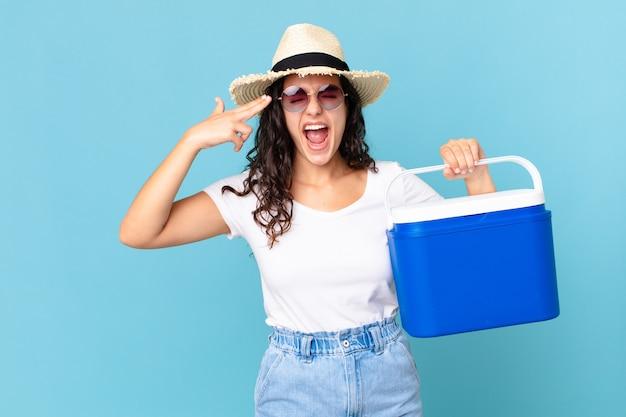 Jolie femme hispanique à l'air malheureuse et stressée, geste de suicide faisant une pancarte tenant un réfrigérateur portable