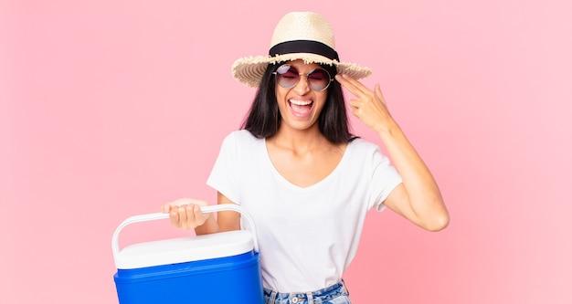 Jolie femme hispanique à l'air malheureuse et stressée, geste de suicide faisant signe d'arme à feu avec un réfrigérateur portable pique-nique