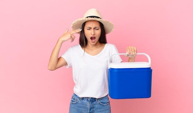 Jolie femme hispanique à l'air malheureuse et stressée, geste de suicide faisant un signe d'arme à feu et tenant un réfrigérateur portable