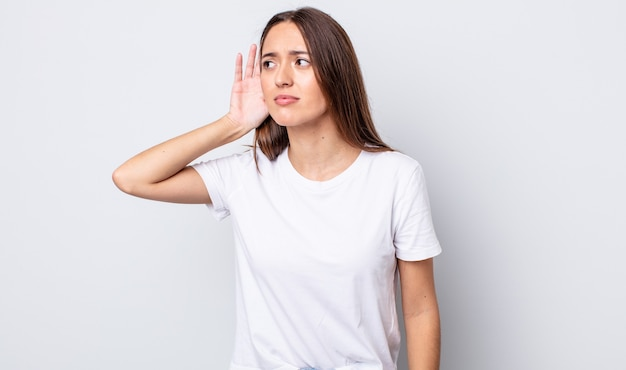 Jolie femme hispanique à l'air sérieuse et curieuse, à l'écoute, essayant d'entendre une conversation secrète ou des potins, espionnant