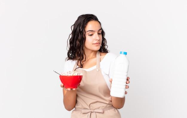 Jolie femme hispanique de chef tenant un bol de petit-déjeuner avec du lait