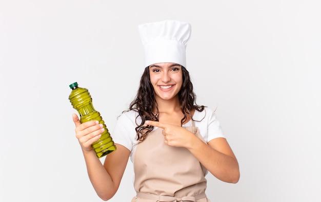 Jolie femme hispanique chef tenant une bouteille d'huile d'olive