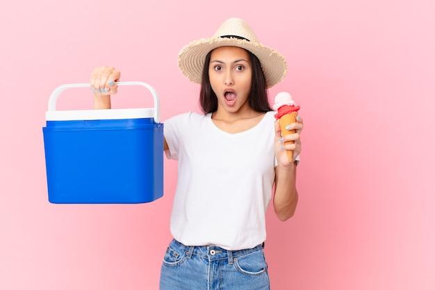 Jolie femme hispanique avec un congélateur portable et une glace