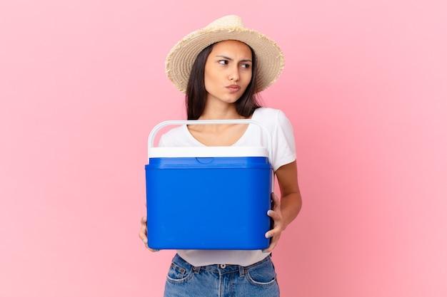 Jolie femme hispanique avec un congélateur portable