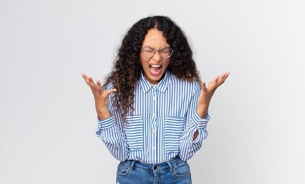 Jolie femme hispanique criant furieusement, se sentant stressée et ennuyée avec les mains en l'air disant pourquoi moi