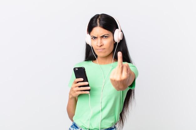 Jolie femme hispanique avec des écouteurs et un smarphone