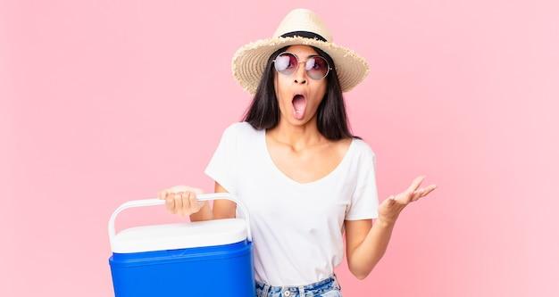 Jolie femme hispanique étonnée, choquée et étonnée d'une incroyable surprise avec un réfrigérateur portable pique-nique