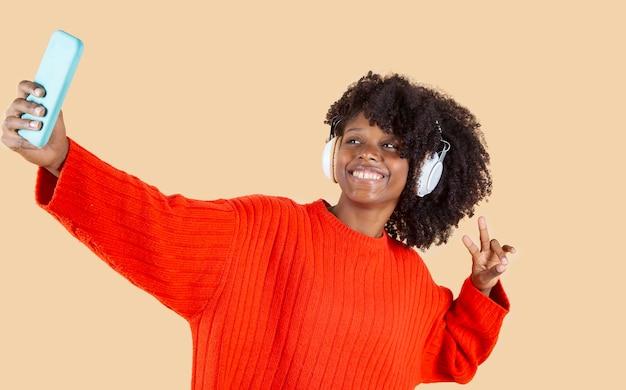 Jolie femme hispanique latino, écoutant de la musique avec des écouteurs, fond beige