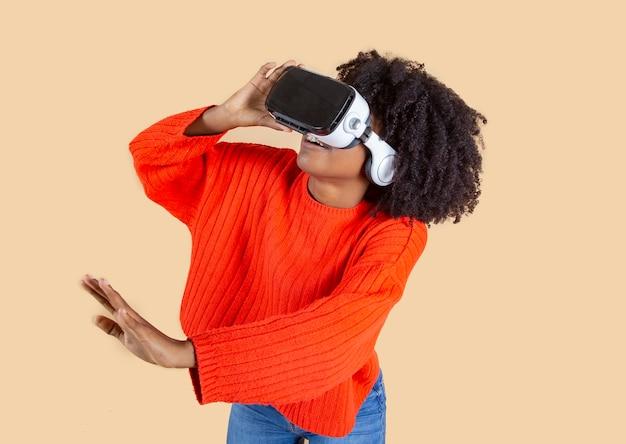 Jolie femme hispanique latino, portant des lunettes de réalité virtuelle, vêtements rouges, fond beige