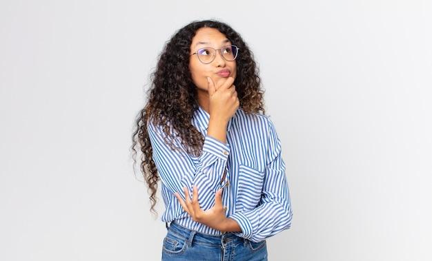 Jolie femme hispanique pensant, se sentant dubitative et confuse, avec différentes options, se demandant quelle décision prendre