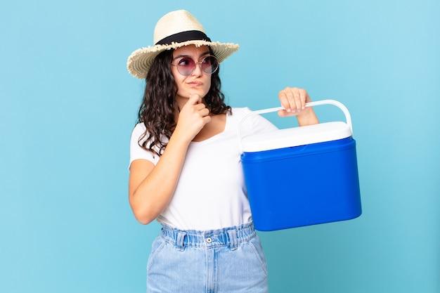 Jolie femme hispanique pensant, se sentant dubitative et confuse tenant un réfrigérateur portable