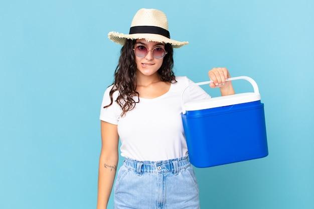 Jolie femme hispanique à la perplexité et à la confusion tenant un réfrigérateur portable