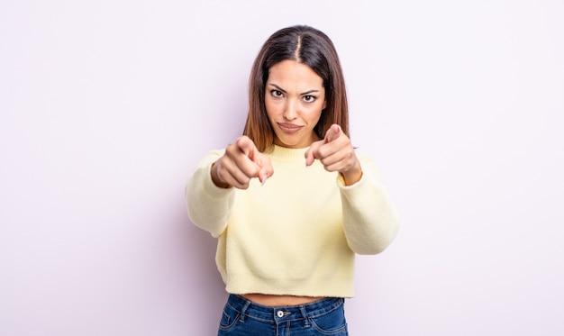 Jolie femme hispanique pointant vers la caméra avec les deux doigts et une expression de colère, vous disant de faire votre devoir