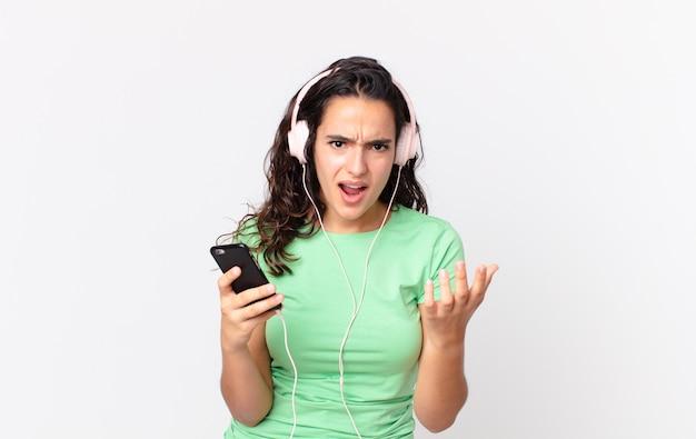 Jolie femme hispanique à la recherche désespérée, frustrée et stressée avec des écouteurs et un smartphone