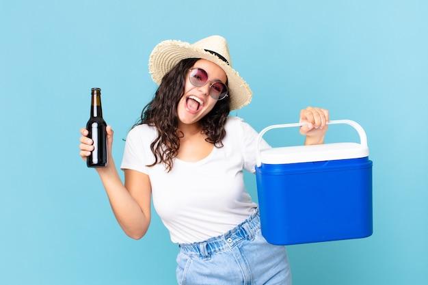 Jolie femme hispanique avec un réfrigérateur portable et une bouteille de bière