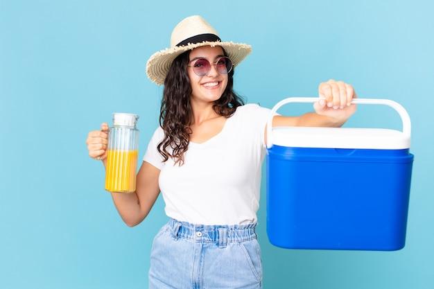 Jolie femme hispanique avec un réfrigérateur portable et un jus d'orange
