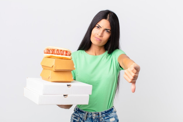 Jolie femme hispanique se sentant croisée, montrant les pouces vers le bas et tenant des boîtes de restauration rapide à emporter