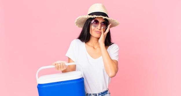 Jolie femme hispanique se sentant ennuyée, frustrée et endormie après un ennuyeux avec un réfrigérateur portable de pique-nique