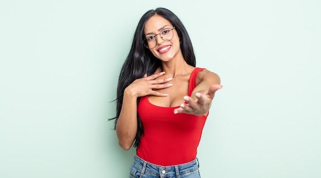 Jolie femme hispanique se sentant heureuse et amoureuse, souriante d'une main à côté du cœur et de l'autre tendue vers l'avant