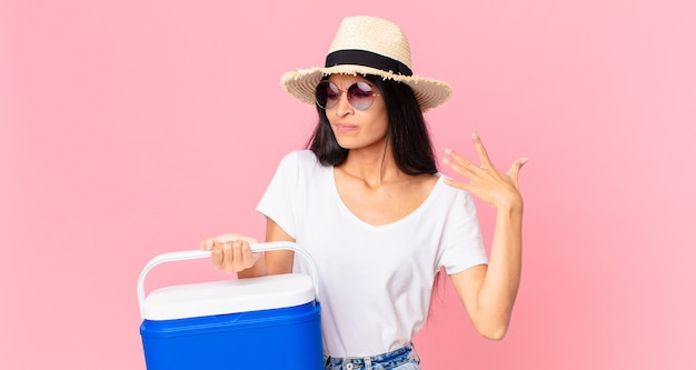 Jolie femme hispanique se sentant stressée, anxieuse, fatiguée et frustrée par un réfrigérateur portable pique-nique