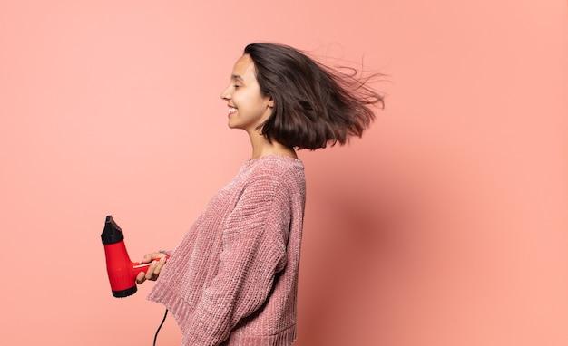 Jolie femme hispanique avec un sèche-cheveux