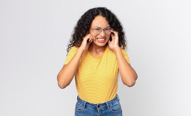 Jolie femme hispanique semblant en colère, stressée et agacée, couvrant les deux oreilles à un bruit assourdissant, un son ou une musique forte