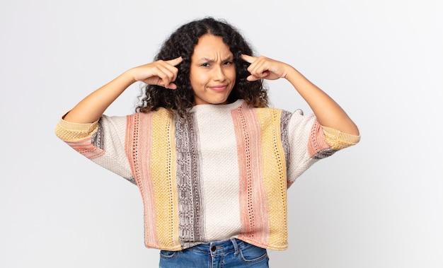 Jolie femme hispanique semblant concentrée et réfléchissant à une idée, imaginant une solution à un défi ou à un problème