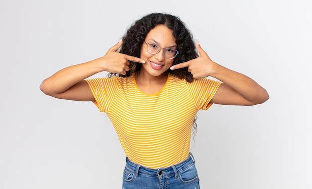 Jolie femme hispanique souriante pointant avec confiance vers son propre large sourire, attitude positive, détendue et satisfaite